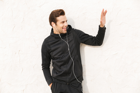 Photo pour Image of handsome sportsman 30s in black sportswear and earphones standing over white wall outdoor - image libre de droit