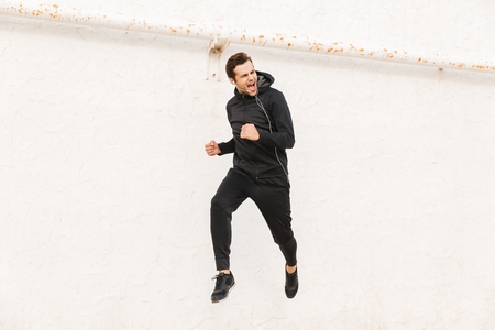 Photo pour Image of european man 30s in black sportswear and earphones running along white wall outdoor - image libre de droit