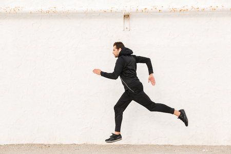 Foto per Image of caucasian man 30s in black sportswear and earphones running along white wall outdoor - Immagine Royalty Free