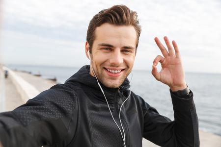 Foto per Image of satisfied sportsman 30s in black sportswear and earphones taking selfie photo on mobile phone while walking at seaside - Immagine Royalty Free