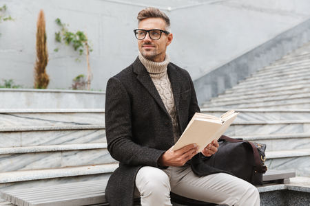 Photo pour Handsome man wearing jacket reading a book while sitting outdoors - image libre de droit