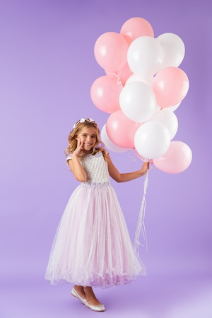 Foto de Full length of a pretty little girl dressed in princess dress standing isolated over violet background, holding bunch of balloons - Imagen libre de derechos