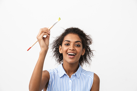 Photo pour Beautiful young african woman atrist holding a paint brush over white background - image libre de droit