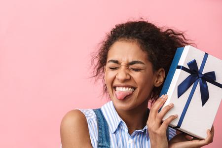 Foto de Beautiful excited young african woman holding gift box over pink background - Imagen libre de derechos