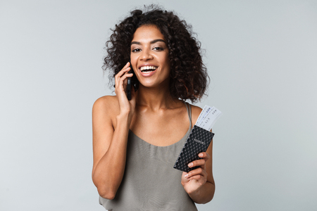 Photo pour Smiling young african woman standing isolated over gray background, showing flight tickets with passport, talking on mobile phone - image libre de droit