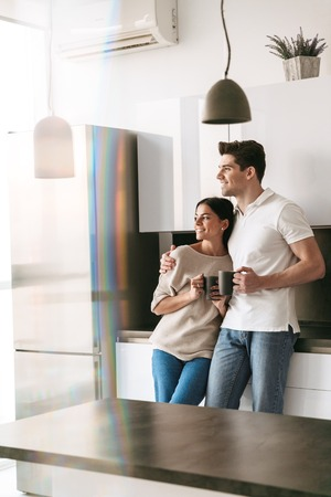 Foto de Happy lovely young couple holding cups while standing at the kitchen at home, looking at the window - Imagen libre de derechos
