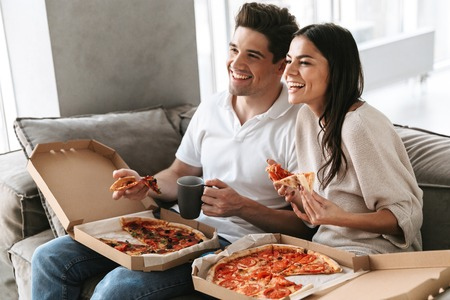 Photo pour Cheerful young couple sitting on a couch at home, eating pizza, watching TV - image libre de droit