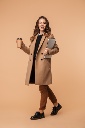 Foto de Full length of a smiling young woman wearing a coat walking isolated over beige background, carrying laptop and drinking coffee - Imagen libre de derechos