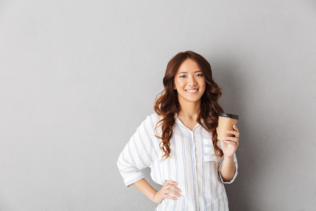 Foto de Cheerful asian woman standing isolated over gray background, drinking coffee - Imagen libre de derechos