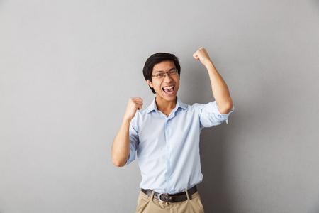 Foto de Happy asian man standing isolated over gray background, celebrating - Imagen libre de derechos