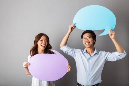 Foto de Cheerful asian couple standing isolated over gray background, holding empty speech bubble - Imagen libre de derechos