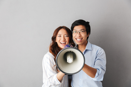 Photo pour Happy asian business couple standing isolated over gray background, holding loudspeaker - image libre de droit