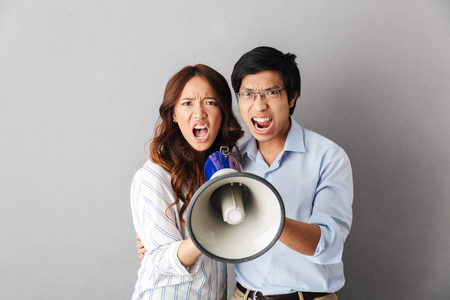Photo pour Angry asian business couple standing isolated over gray background, holding loudspeaker - image libre de droit