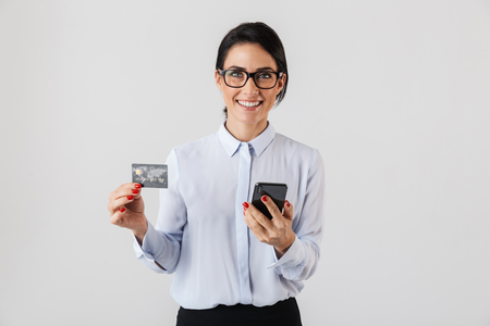 Photo pour Image of smart office woman wearing eyeglasses holding mobile phone and credit card isolated over white background - image libre de droit