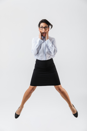 Foto de Full length portrait of a pretty businesswoman jumping isolated over white background, celebrating success - Imagen libre de derechos