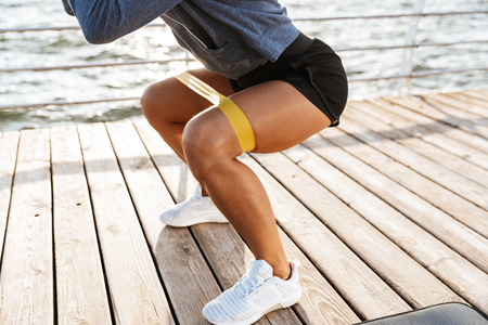Photo pour Close up of a sportswoman doing exercises with a rubber band at the beach - image libre de droit