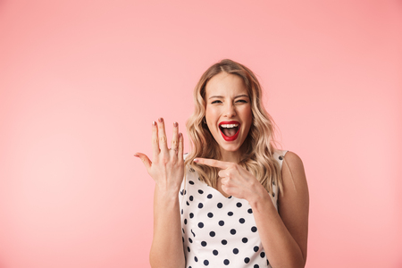 Photo for Beautiful excited young blonde woman wearing dress standing isolated over pink background, showing engagement ring on her finger - Royalty Free Image