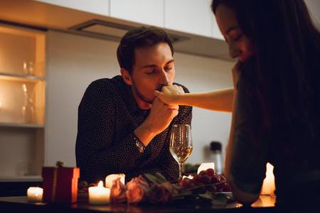 Foto de Beautiful passionate couple having a romantic candlelight dinner at home, man kissing hand - Imagen libre de derechos