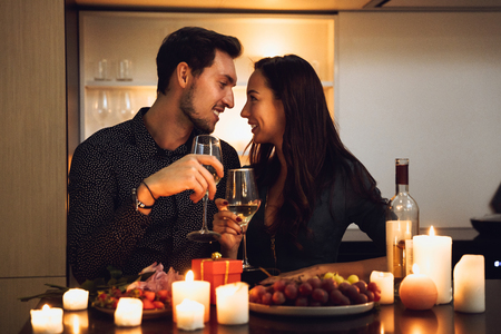 Foto de Beautiful passionate couple having a romantic candlelight dinner at home, drinking wine, toasting - Imagen libre de derechos
