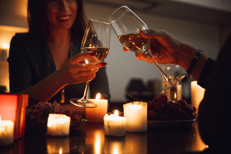 Photo for Beautiful passionate couple having a romantic candlelight dinner at home, drinking wine, toasting - Royalty Free Image
