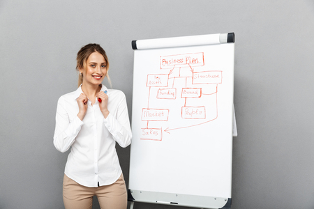 Foto de Image of happy businesswoman in formal wear standing and making presentation using flipchart in the office isolated over gray background - Imagen libre de derechos