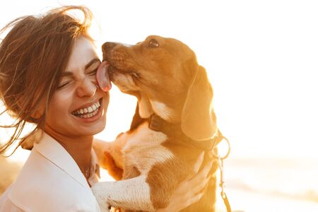 Foto de Image of happy woman 20s hugging her dog while sitting on sand by seaside - Imagen libre de derechos