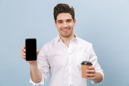 Photo pour Portrait of a cheerful handsome young man standing isolated over blue background, holding takeaway coffee cup, showing blank screen mobile phone - image libre de droit