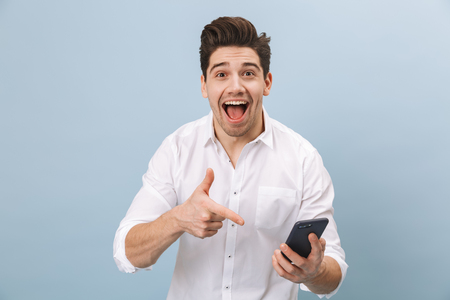 Photo pour Portrait of a cheerful handsome young man standing isolated over blue background, holding mobile phone, celebrating - image libre de droit