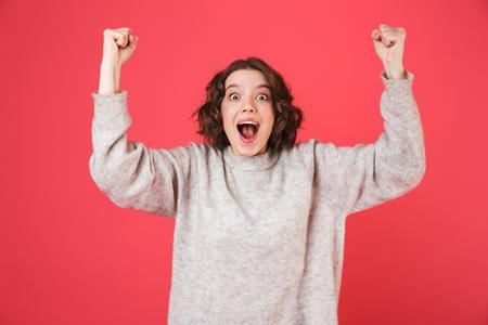 Foto de Portrait of a cheerful young woman standing isolated over pink background, celebrating - Imagen libre de derechos