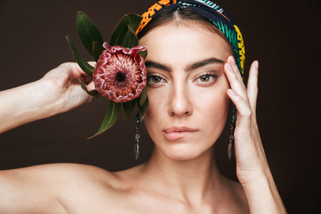 Photo pour Beauty portrait of a topless young beautiful woman wearing headband and earrings standing isolated over black background - image libre de droit