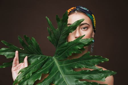Photo pour Beauty portrait of a topless young beautiful woman wearing headband and earrings standing isolated over black background, posing with green tropical leaf - image libre de droit