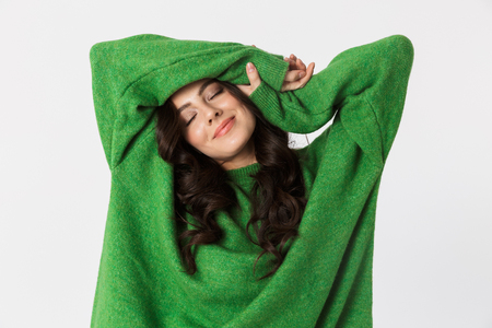 Foto de Image of beautiful young woman dressed in green sweater posing isolated over white wall background. - Imagen libre de derechos