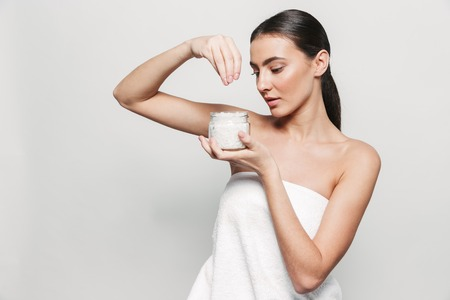 Photo pour Beauty portrait of a young healthy attractive brunette woman standing isolated over white background, holding jar of spa salt - image libre de droit