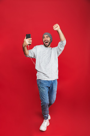 Foto de Full length photo of european man 30s singing while listening to music with earphones and mobile phone isolated over red background - Imagen libre de derechos
