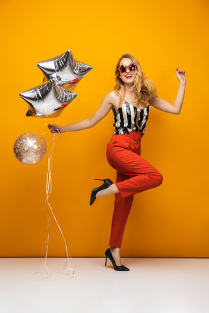 Photo for Full length portrait of a beautiful young blonde woman standing over yellow background, wearing sunglasses, posing, holding balloons - Royalty Free Image