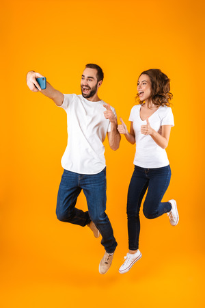 Photo pour Full length photo of young couple laughing and taking selfie on smartphone isolated over yellow background - image libre de droit
