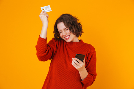 Foto de Image of excited emotional young pretty woman posing isolated over yellow wall background using mobile phone holding credit card. - Imagen libre de derechos