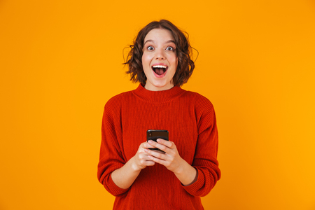Foto de Portrait of caucasian woman 20s wearing sweater holding and using cell phone while standing isolated over yellow background - Imagen libre de derechos