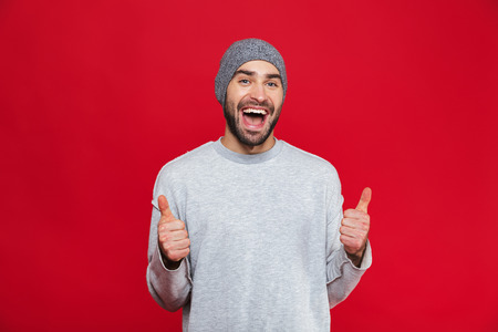 Photo pour Image of attractive man 30s having stubble laughing and showing thumbs up on camera isolated over red background - image libre de droit