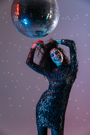 Photo for Beautiful young woman wearing sparkling dress dancing disco isolated - Royalty Free Image