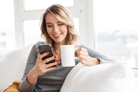 Photo pour Image of cute pretty woman sitting indoors at home holding cup drinking tea using mobile phone. - image libre de droit