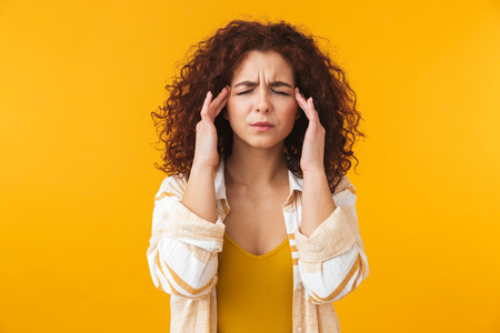 Photo pour Image of tense woman 20s with curly hair rubbing her temples because of headache, isolated over yellow background - image libre de droit