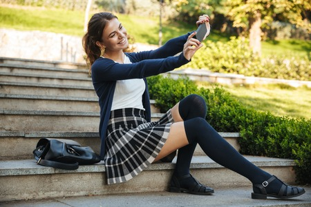 Photo pour Cheerful young school girl sitting outdoors on staircase, using mobile phone, taking selfie - image libre de droit