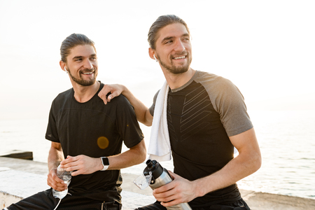 Photo pour Two twin brothers doing exercises at the beach together - image libre de droit