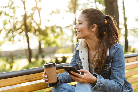 Foto de Smiling young woman wearing jacket sitting on a bench at the park, using mobile phone, drinking takeaway coffee - Imagen libre de derechos