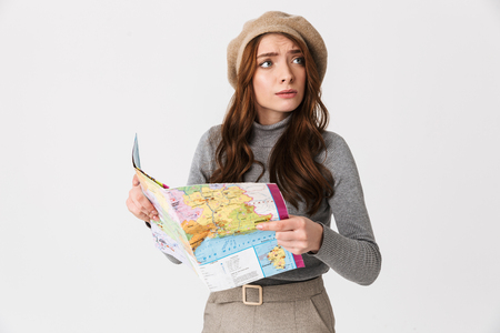 Photo pour Photo of puzzled woman 30s wearing hat holding and reading world map isolated over white background - image libre de droit