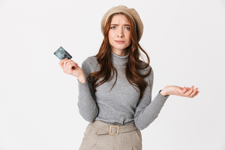 Photo pour Image of confused beautiful woman holding credit card isolated over white wall background. - image libre de droit