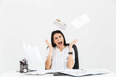 Photo for Photo of neurotic brunette businesswoman 30s screaming and stressing while working with paper documents in office isolated over white background - Royalty Free Image