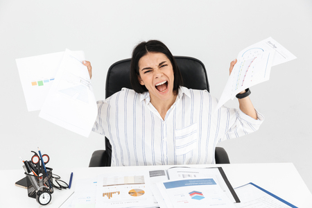 Photo for Photo of european brunette businesswoman 30s screaming and stressing while working with paper documents in office isolated over white background - Royalty Free Image