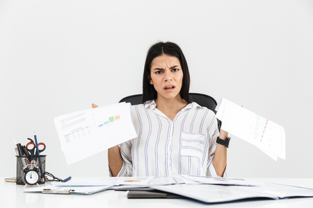Photo for Photo of tense brunette businesswoman 30s screaming and stressing while working with paper documents in office isolated over white background - Royalty Free Image